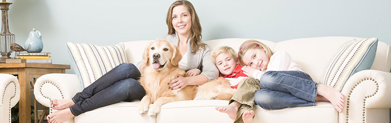 family sitting on couch after upholstery cleaning in Carlsbad