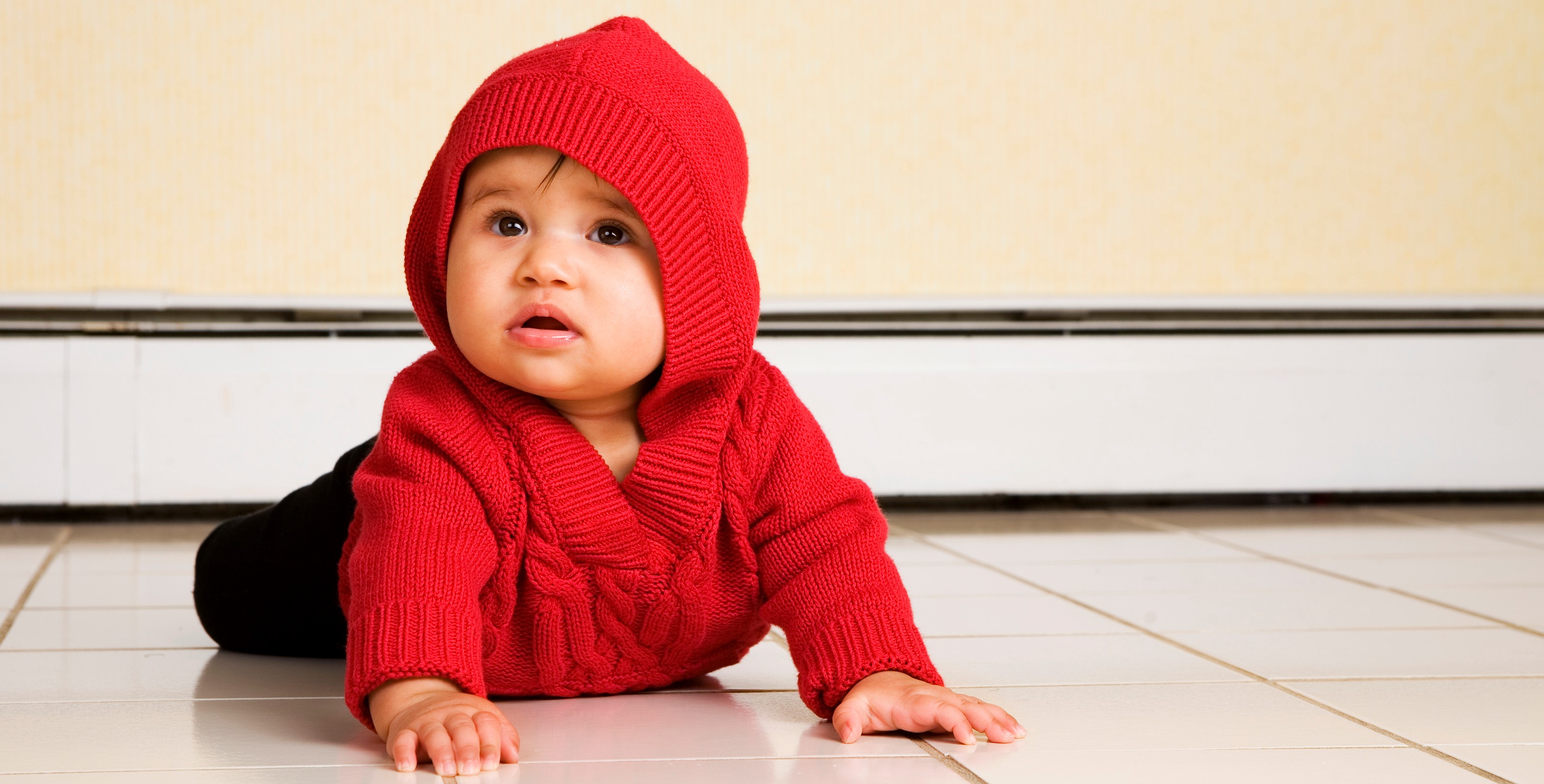 A biracial baby girl looking up as she trys to creep across a white, tile floor.